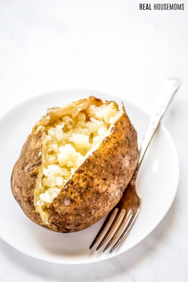 crock pot baked potato split open on a plate with a fork