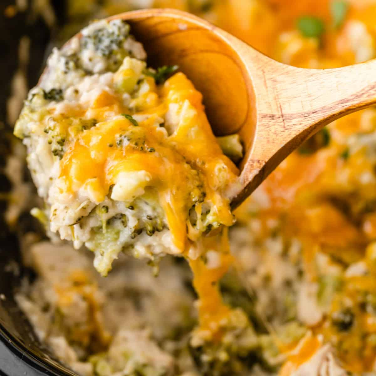 square image of Crock Pot Cheesy Broccoli Chicken and Rice portion on a spoon