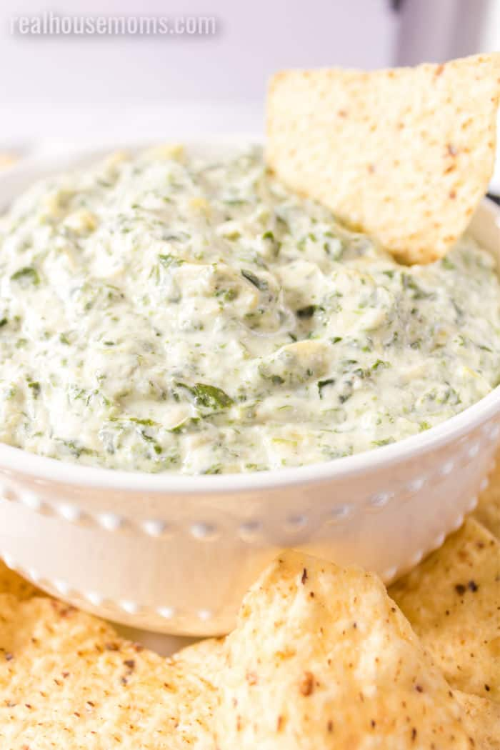 tortilla chip stuck into a bowl of slow cooker spinach artichoke dip