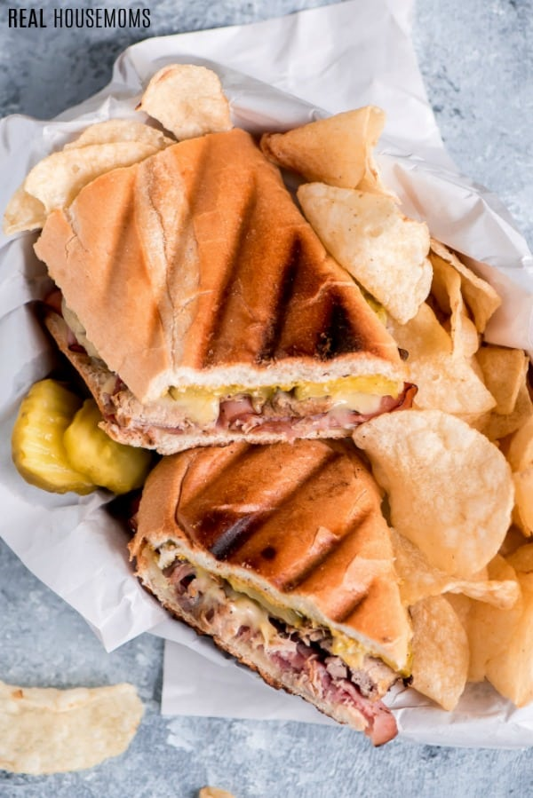 overhead picture of cuban sandwich served with chips