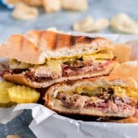 Take your sandwich game to the next level with this pork and cheese loaded hot Cuban Sandwich Recipe. With grilled crispy bread, melted cheese, and flavorful pork, you'll be left wanting more!