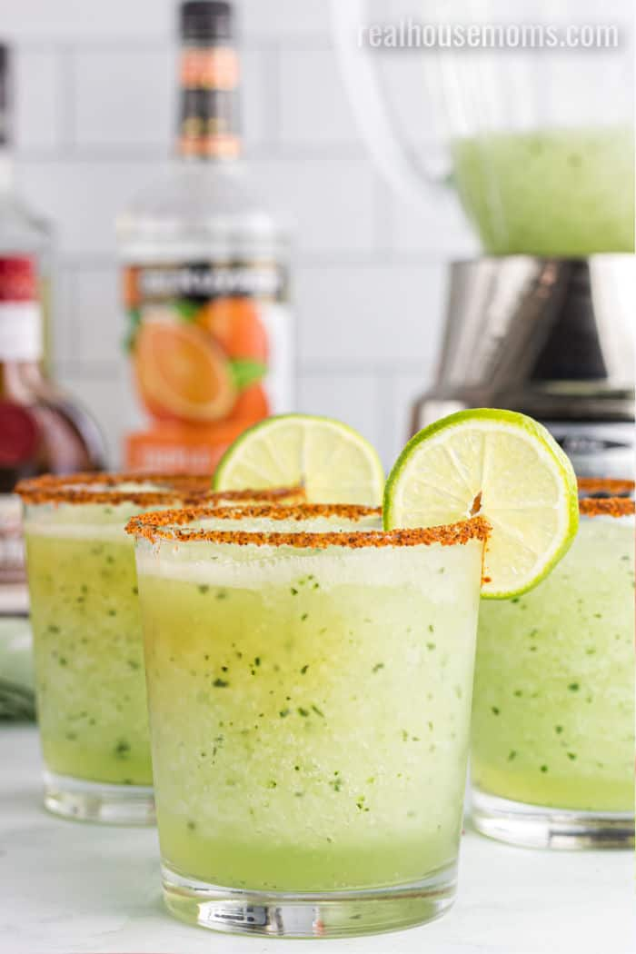 frozen cucumber margaritas in glasses with lime garnish
