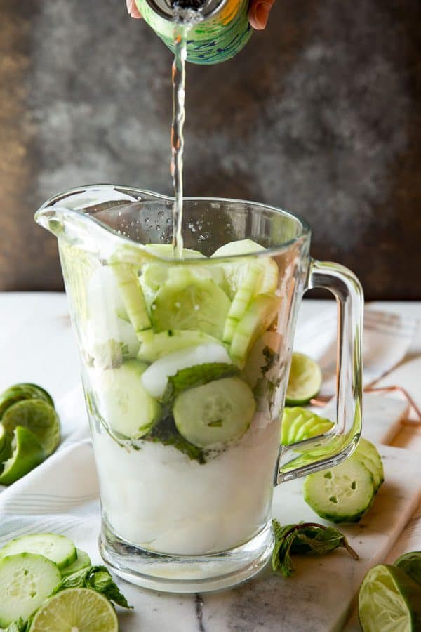 Assembling Cucumber Mint Mojitos in a pitcher, pouring in soda water.