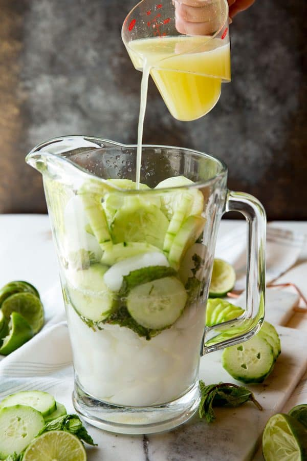 Assembling Cucumber Mint Mojitos in a pitcher, pouring in lime juice.