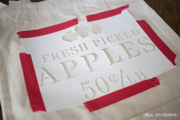 Apple Picking Tote stencil taped to tote bag