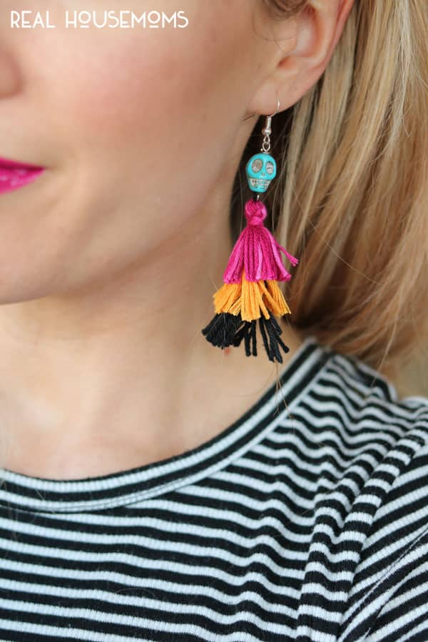 Close up of DIY Festive Skull Earrings being worn with a black and white striped shirt