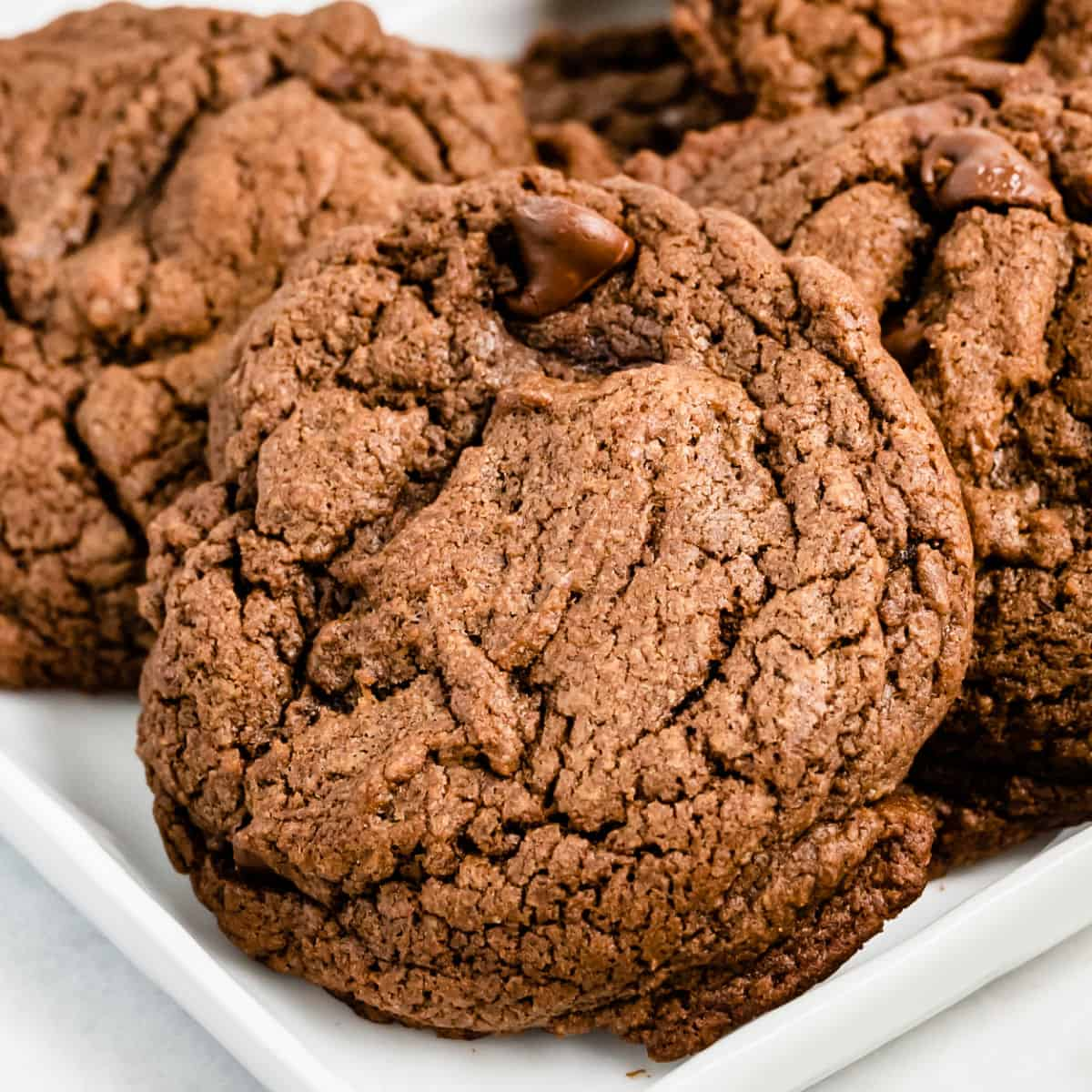 close up of adouble chocolate brownie cookie on a platter of cookies