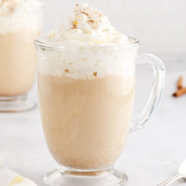 square image of a drunken pumpkin mocha in a glass mug with whipped cream