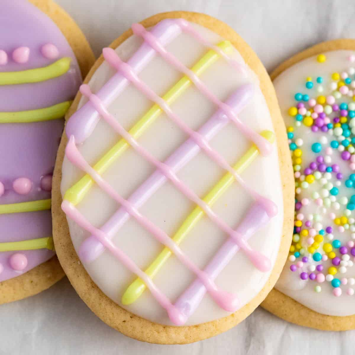 square image of an easter egg sugar cookie with white icing and pink, purple, and yellow criss-cross lines on top
