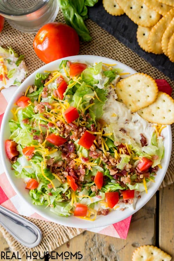 Bowl of Easy BLT Dip with a few bites take so the creamy dip based under the fresh ingredients is revealed