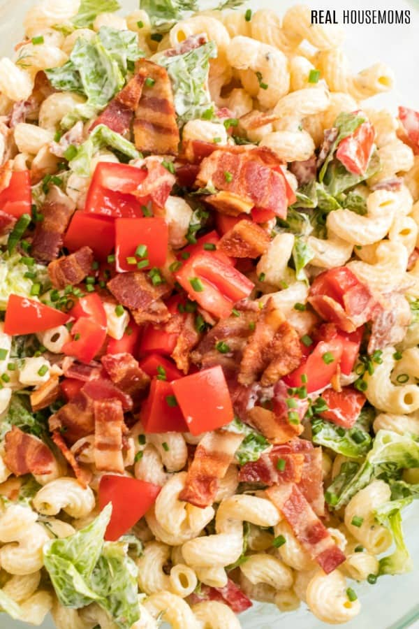 BLT pasta salad garnished with bacon, tomatoes, and chives