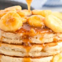 bananas foster topping being poured over pancakes with recipe name at bottom