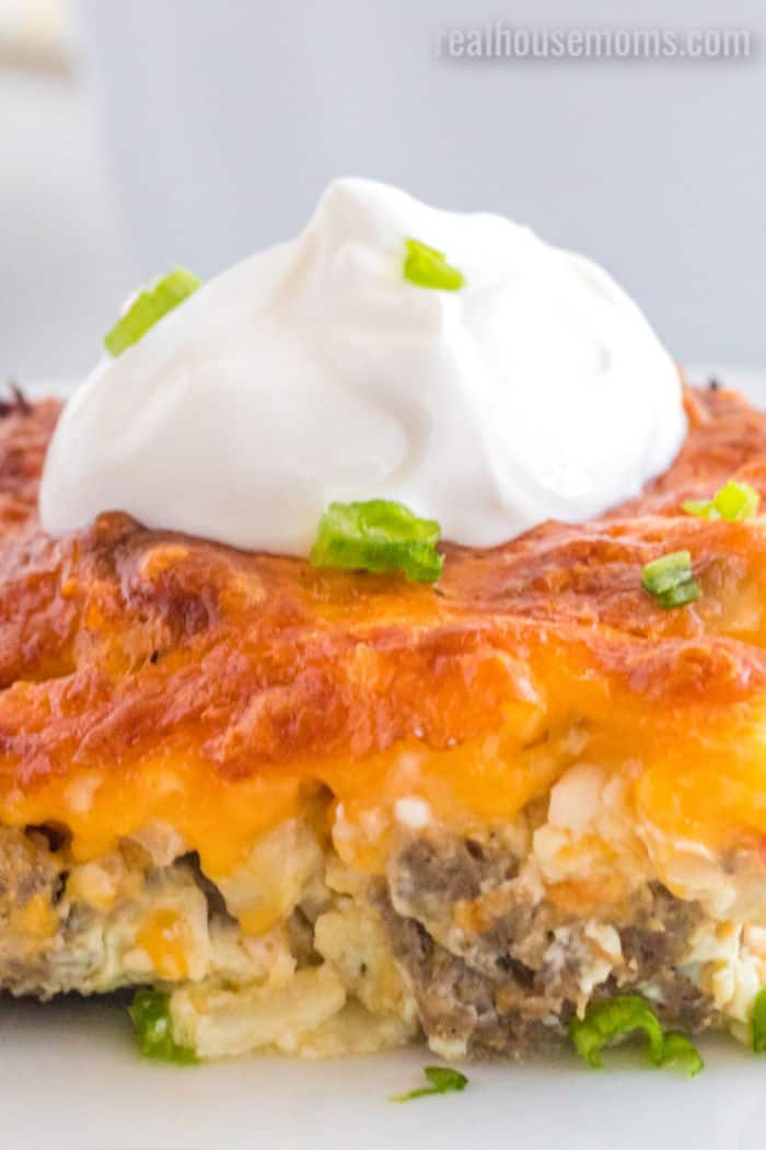 sloce up of slice of cheesy soutwest breakfast casserole topped with sour cream and green onion