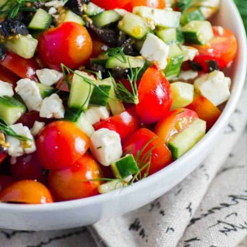 White bowl with tomatoes cucumbers and feta cheese tossed together to make Easy Dinner Ideas Tomato and Cucumber Salad