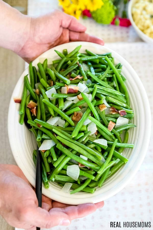 bowl of green beans being placed on dinner table