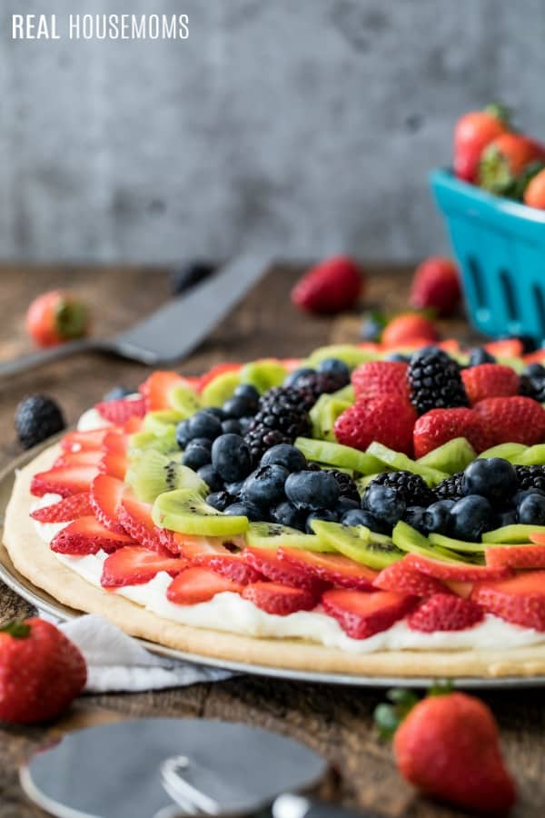 fresh fruit over cream cheese frosting on a sugar cookie crust to make fruit pizza