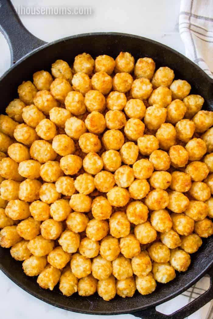 cast iron skillet with tater tots arranged over filling