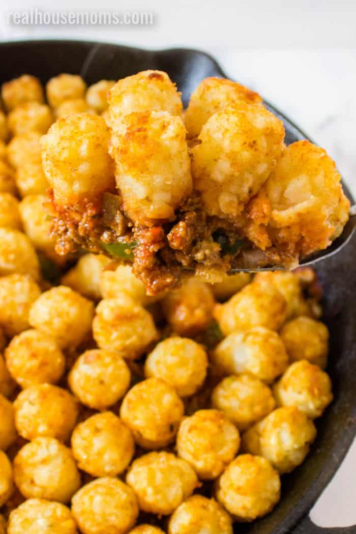 close up of a serving spoon of sloppy joe caserole with tater tots