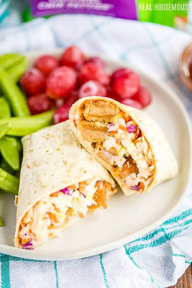 BBQ Chik Tortilla Wrap cut in half and on plate with grapes and snap peas