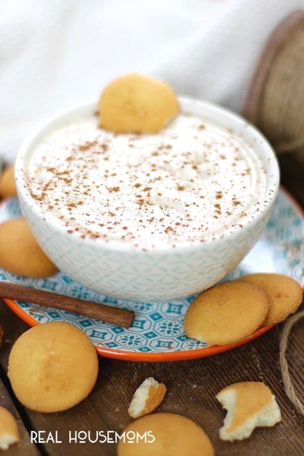 Eggnog Cheesecake Dip in a serving bowl, sprinkle with cinnamon and served with vanilla wafer cookies