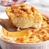square image of a slice of eggnog french toast bake on a wooden spatula over the baking dish