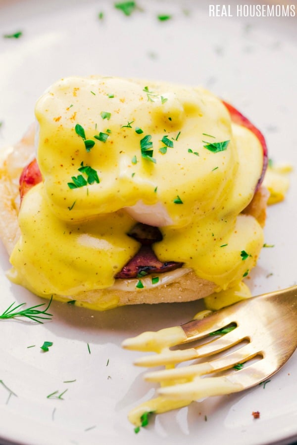eggs benedict with hollandaise one a plate with a fork