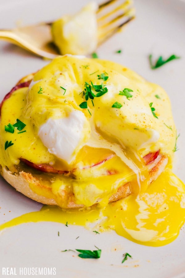 eggs benedict with egg cut open to show the runny yolk
