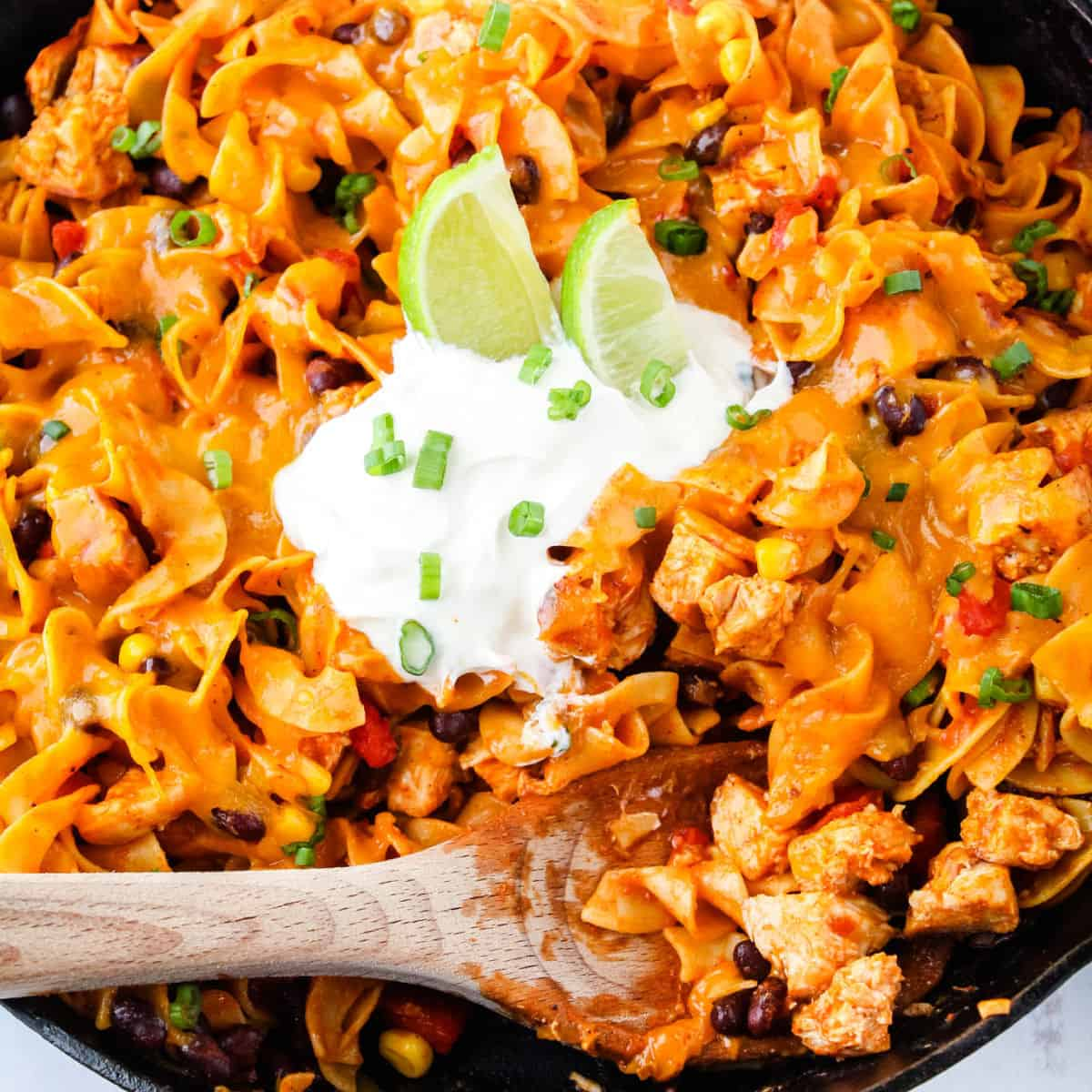square image of enchilada pasta in a cast iron skillet with a wooden spoon