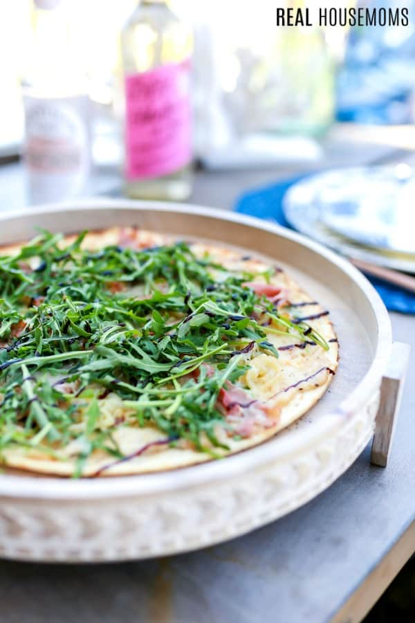 pig & prosciutto pizza served on a wooden plate with cost plus world market tableware