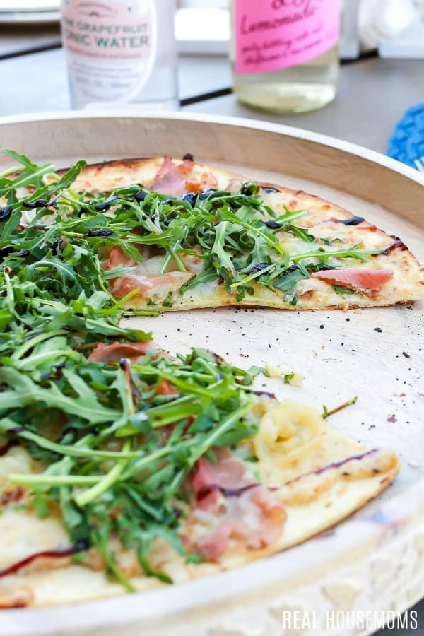 thin crust fig & prosciutto pizza with a slice taken out