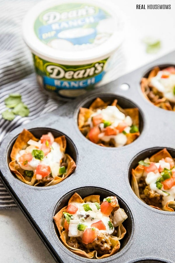 taco cups in a muffin tin topped with dean's ranch dip