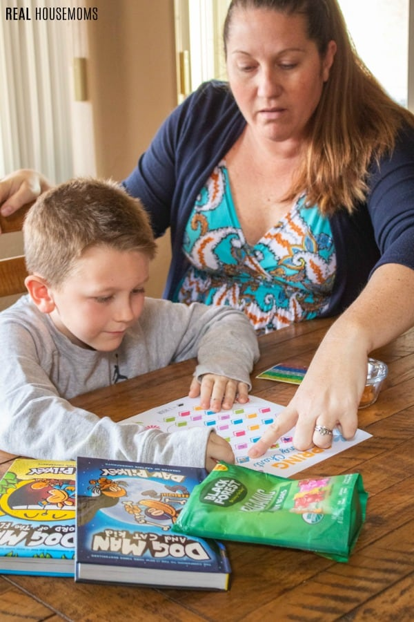 mom helping son add star stickers to printable reading chart