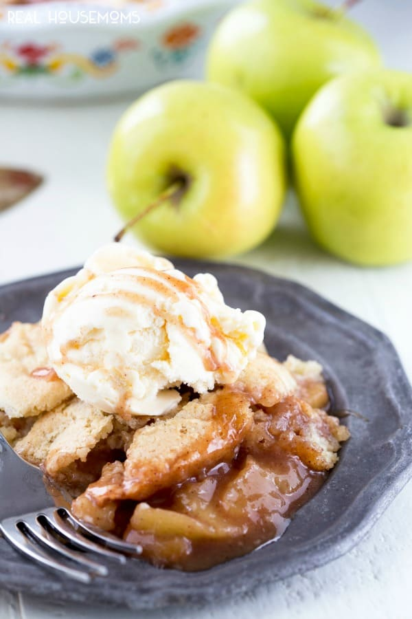 A plated portion of Apple Cobbler topped with vanilla ice cream with apples in the background