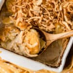 close up of French Onion Scalloped Potatoes in a white pan with a wooden spoon full of a scoop of potatoes