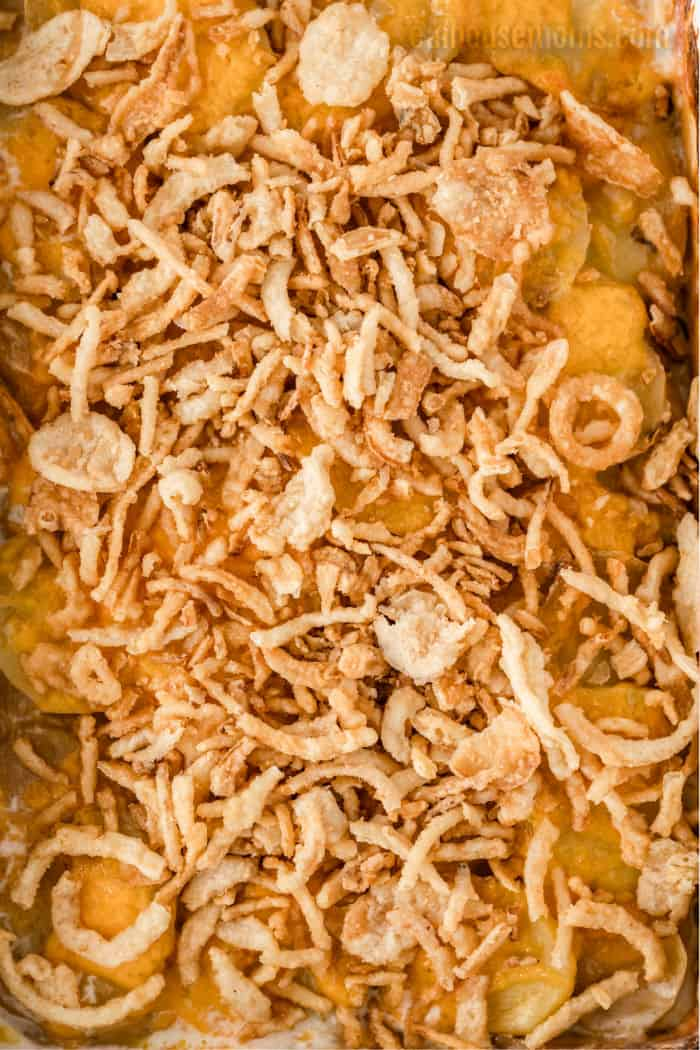 close up of French's crispy onions spread over the top of scalloped potatoes with cheese