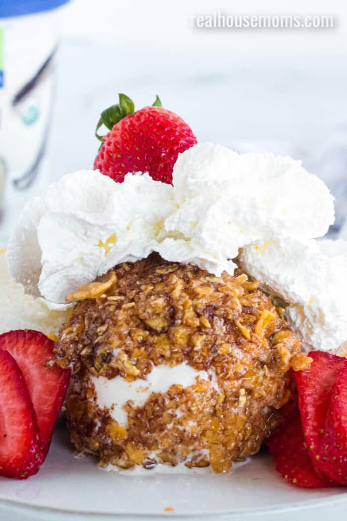 fried ice cream topped with whipped cream and strawberries