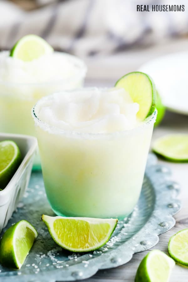 frozen margarita in a glass rimmed with salt garnished with a lime slice
