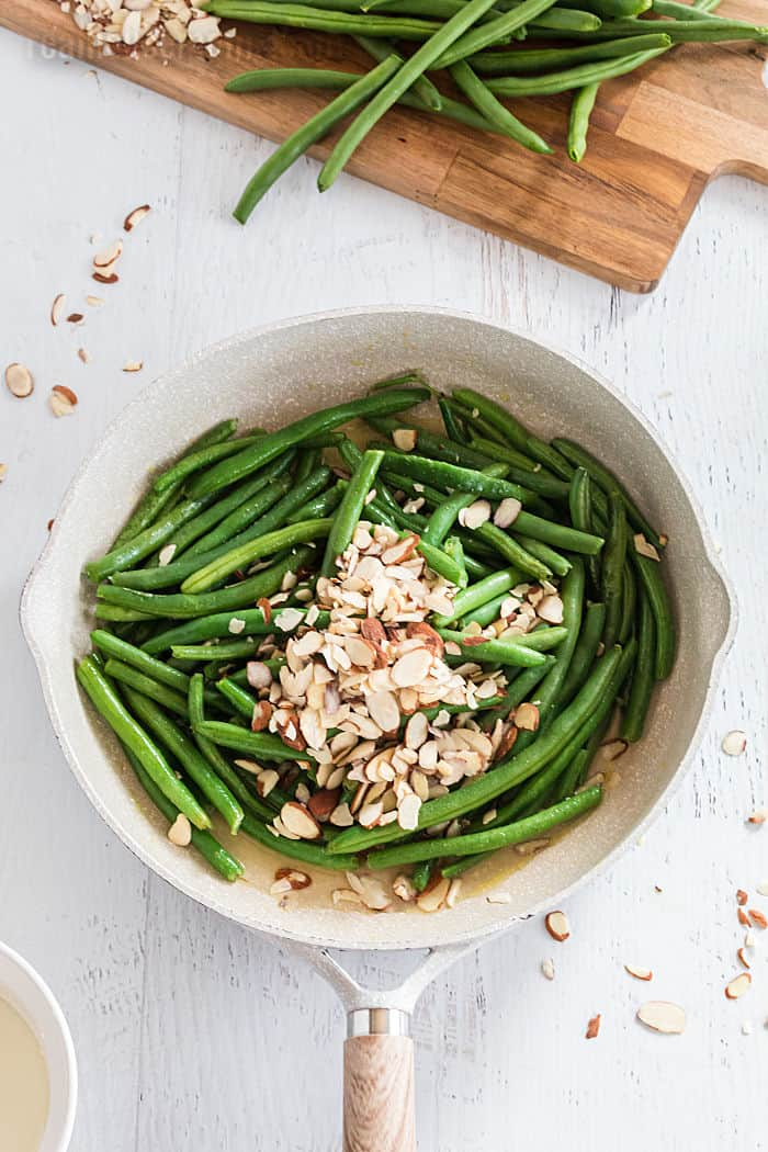 green beans topped with almonds in a skillet