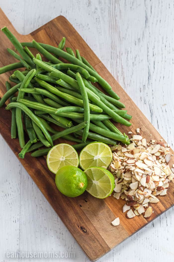 green beans, lime halves, and sliced almonds on a cutting board