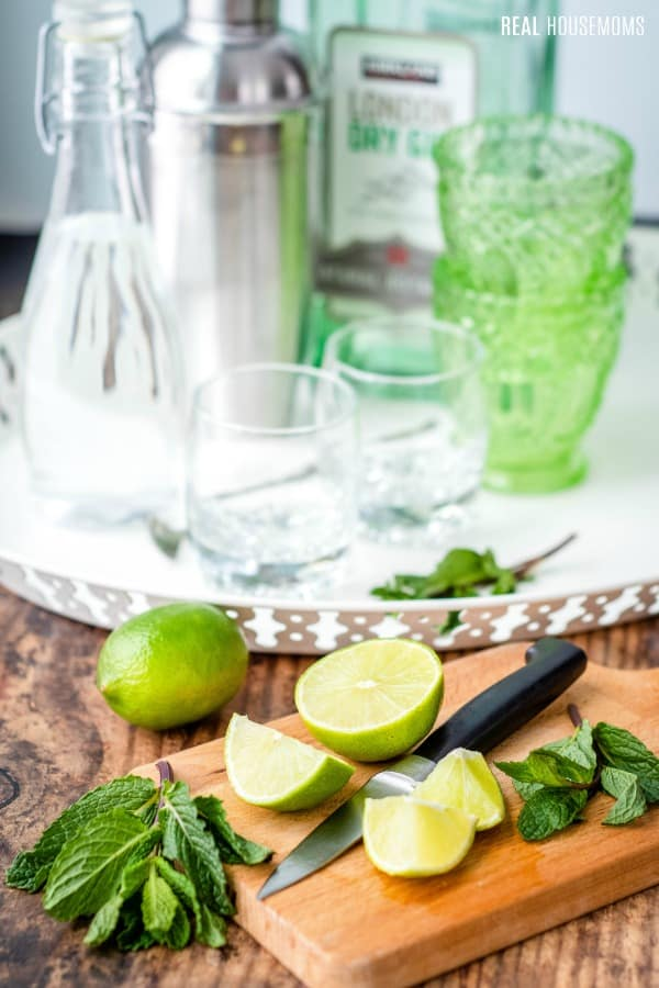 limes and mint of a cutting board for gimlets