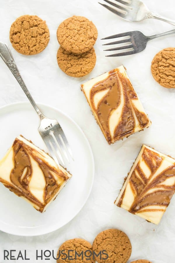 Gingersnap Cheesecake Bars served on plates and surrounded by gingersnap cookies