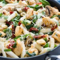 goat cheese chicken penne pasta in a skillet with muchrooms, basil, parmensa cheese, and sun-dried tomatoes