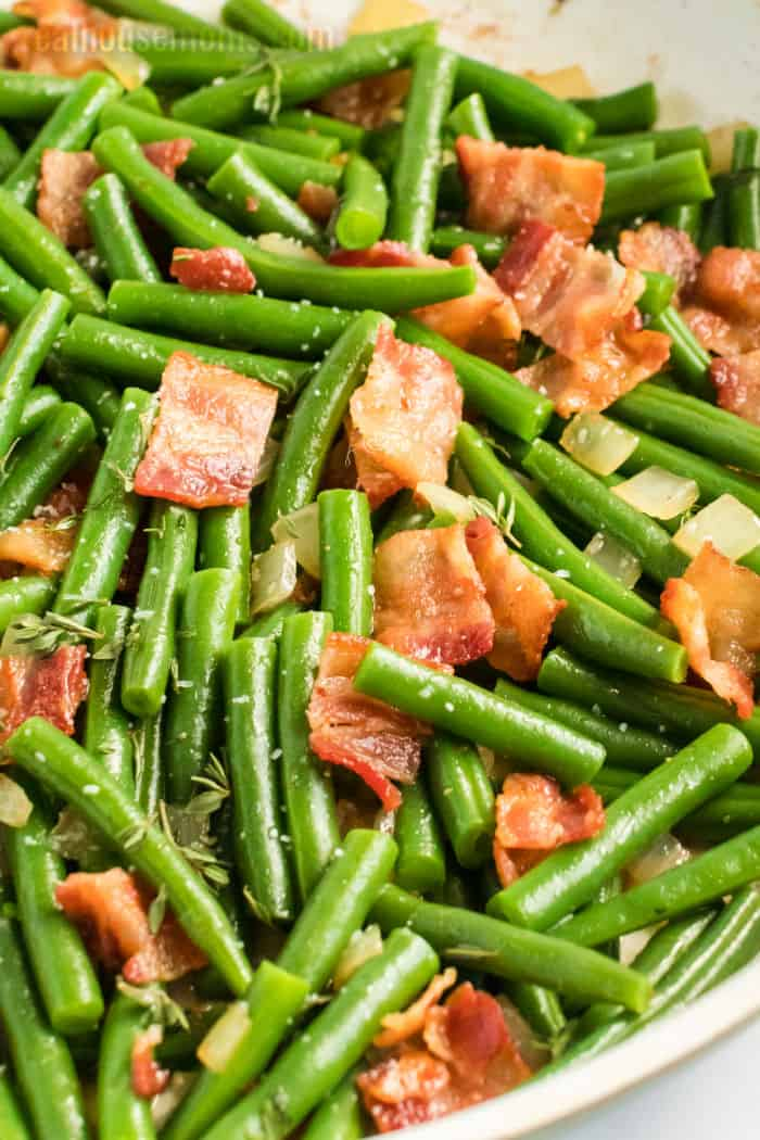 close up of green beand with bacon and onions in a pan