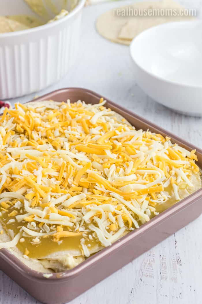 green chili chicken casserole topped with shredded cheese before baking