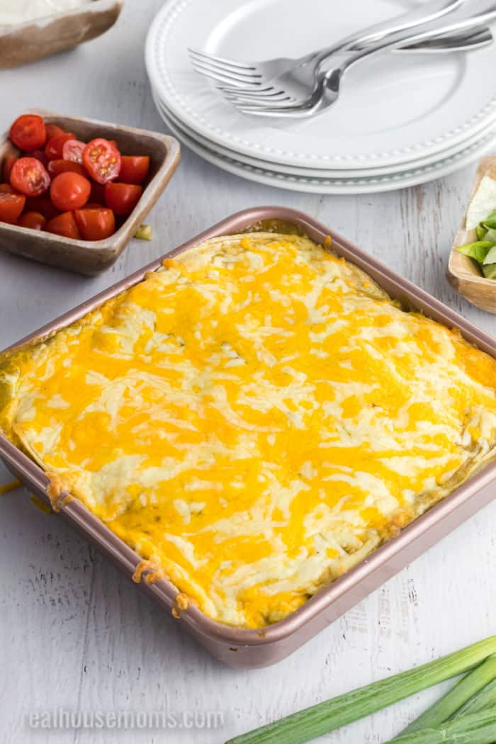 green chicken enchilada casserole after baking with a bowl of tomatoes beside the dish