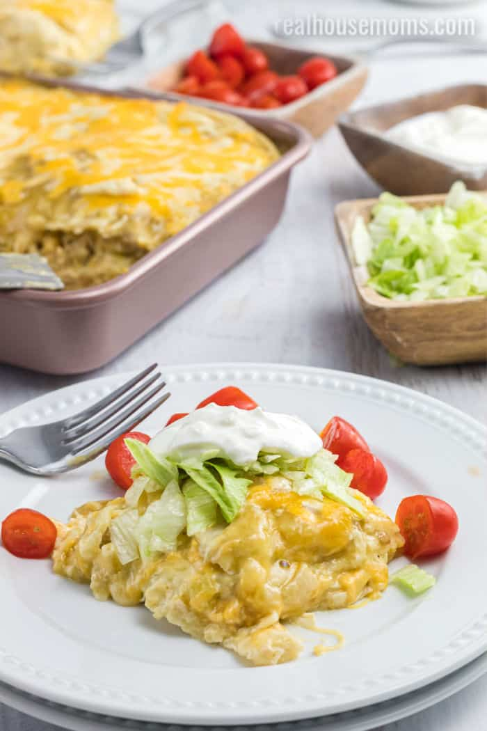 portion of green chili chicken enchilada casserole on a dinner plate garnished with lettuce, sour cream, and halved cherry tomatoes