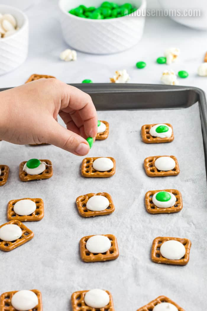 green m&Ms being put on white candy melts to make green eggs