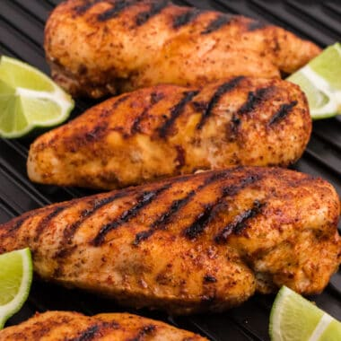 square image of honey lime chicken breasts on a grill pan with lime wedges