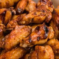 square close up image of grilled honey sriracha chicken wings in a serving bowl