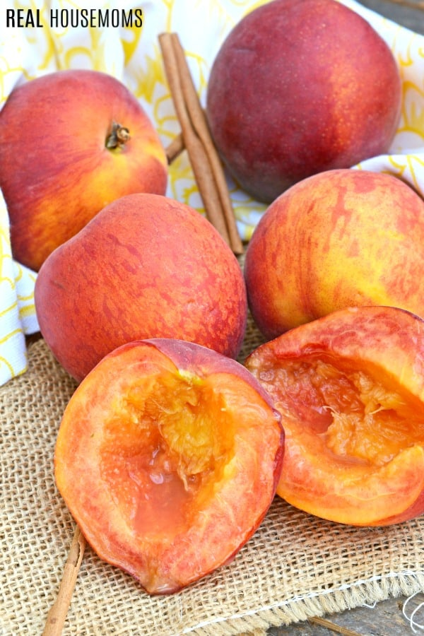 peaches on a counter with one halved and pitted